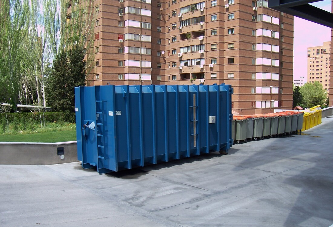 A residential roll off dumpster outside an apartment building