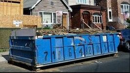 A large blue dumpster filled with construction waste